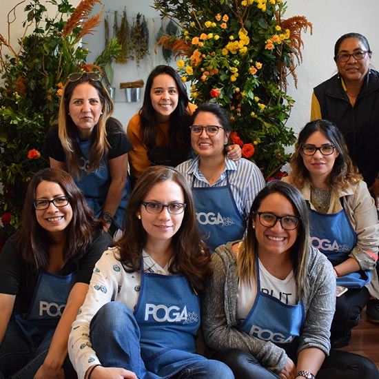 Alumnas del Curso Básico de Floristería frente a un arco de flores