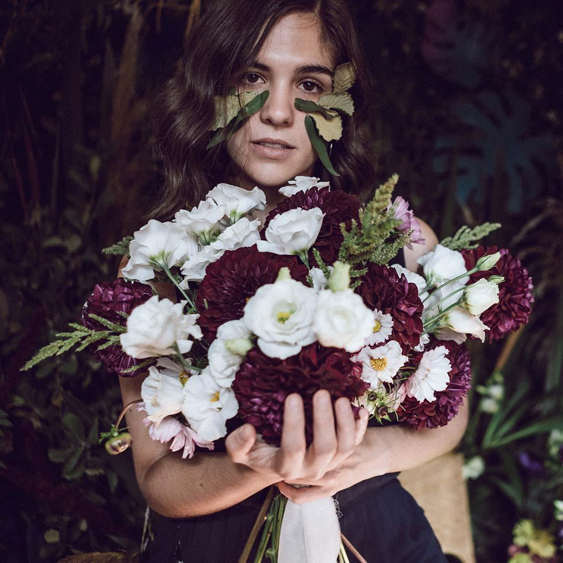 Modelo ofreciendo un ramo de flores