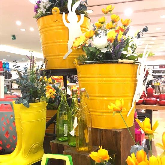 Cubetas amarillas con flores artificiales para pascua en Palacio de Hierro