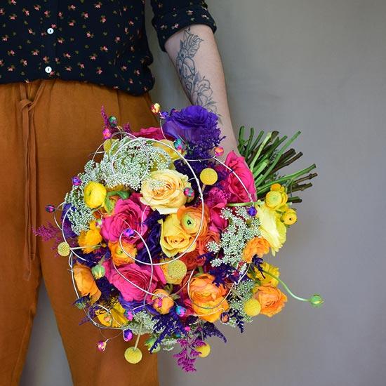 Ale Ponce cargando un ramo de flores colorido
