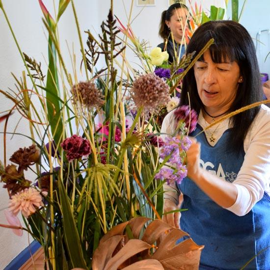 Alumna elaborando arreglo floral con varas