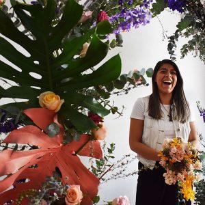 Alumna posando debajo de un arco con flores